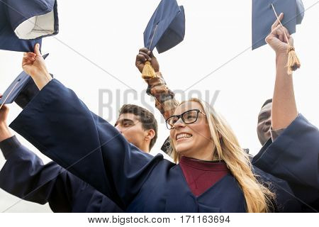 education, graduation and people concept - group of happy international students in bachelor gowns waving mortar boards or hats