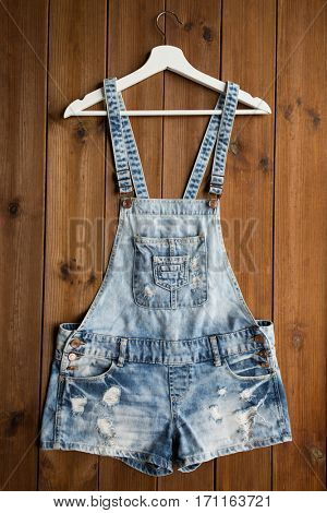 clothes, wear and fashion concept - denim or jeans overalls with hanger on wooden background