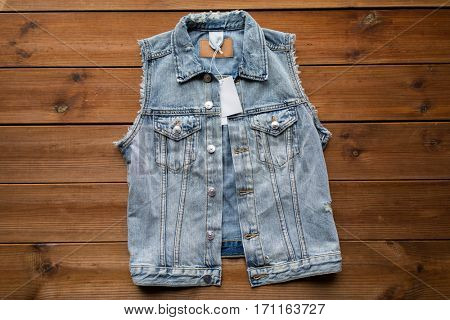 clothes, wear and fashion concept - close up of denim vest or waistcoat with price tag on wooden background