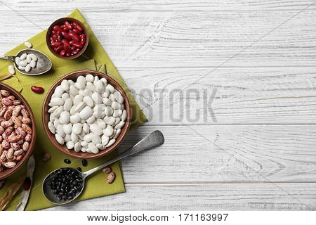 Assortment of haricot beans in bowls and spoons on white wooden background