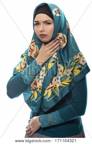 Female wearing a hijab conservative fashion for muslims middle east and eastern european culture. She is isolated on a white background and grabbing her throat like she is sick
