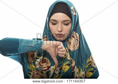 Female wearing a hijab conservative fashion for muslims middle east and eastern european culture. She is isolated on a white background and holding thumbs down in disapproval