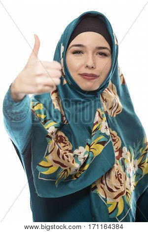 Female wearing a hijab conservative fashion for muslims middle east and eastern european culture. She is isolated on a white background with thumbs up for approval