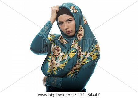 Female wearing a hijab conservative fashion for muslims middle east and eastern european culture. She is isolated on a white background and looking angry and upset.