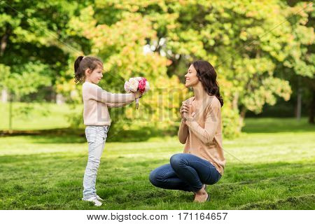 family, holidays and people concept - happy little girl giving flowers to mother in summer park