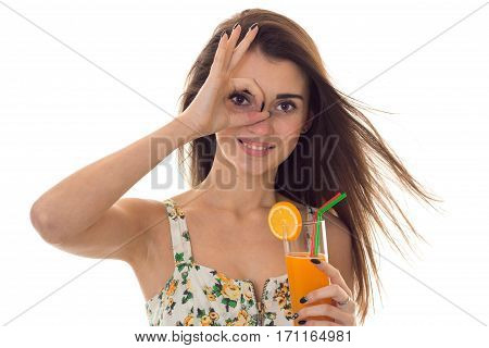 charming young brunette girl in summer clothes with floral pattern shoing OK and drinks orange cocktail isolated on white
