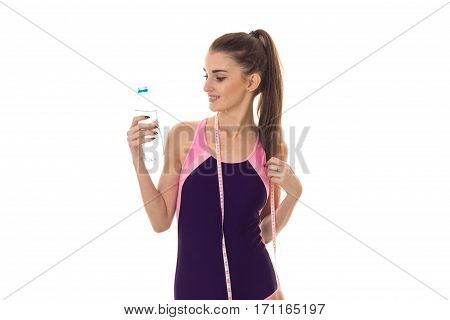 cutie slim young brunette girl in body swimsuit with measure tape on her neck and bottle of water in hands isolated on white