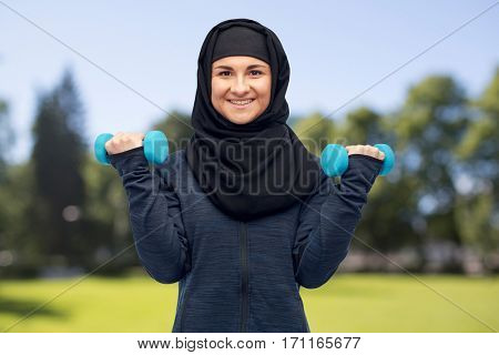 sport, fitness and people concept - happy muslim woman in hijab with dumbbells doing exercises over summer natural background