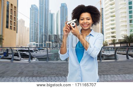 people and photography portrait concept - happy african american young woman with film camera over dubai city street background