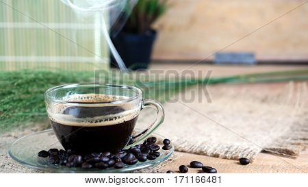 Hot espresso. A cup of strong espresso coffee put on the wood table with shiny dark roasted Italian coffee beans. Aroma and flavor coffee beverage.