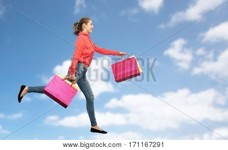 sale, motion and people concept - smiling young woman with shopping bags running in air over blue sky and clouds background