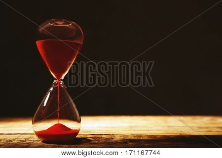 Time passing concept. Crystal hourglass with red sand on wooden table and dark background