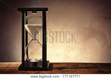 Time passing concept. Black hourglass with white sand on wooden table and dark background