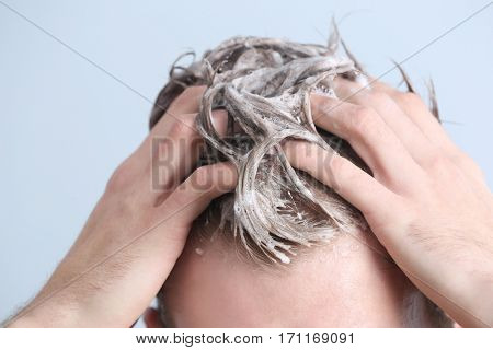 Young man washing hair on color background, closeup