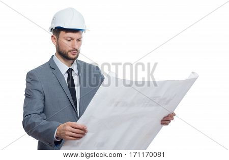 Portrait of engineer wearing in suite and white safety hat holding big drawing plan. Male with beard reading architecture plan of building. Isolate on white background.