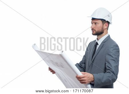 Architect in gray suite and white safety hat looking away, holding big drawing plan by hands. Male with beard reading architecture plan of building. Isolate on white.