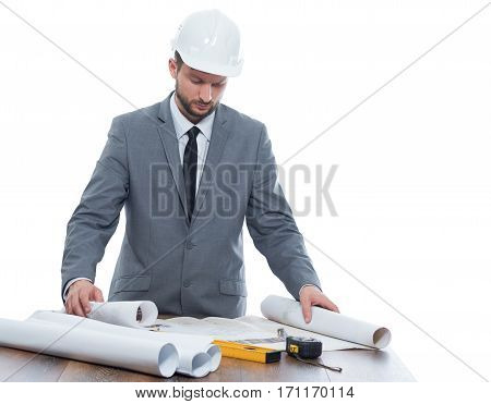 Confident architect reading architecture plan of building and standing at work place, near on table different tools. Engineer with beard in gray suite and white safety hat. Isolate on white.