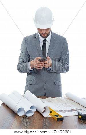 Front view of architect in gray suite and white safety hat using call phone and taking photo of architecture plan on table. Engineer at work place with table and many tools near. Isolate on white.