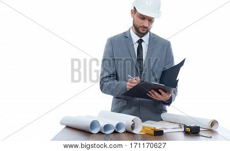 Architect writing report and reading architecture plan of building, standing at work place, on table different tools. Engineer with beard in gray suite and white safety hat. White background.