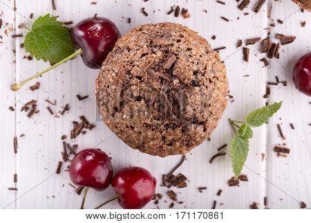 Chocolate muffin with sugar crust and cherry. Top view.