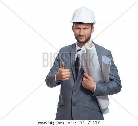 Handsome and young architect wearing in gray suite and white safety hat holding drawing plans. Engineer gesturing super or good by finger, smiling at camera. Isolate on white background.