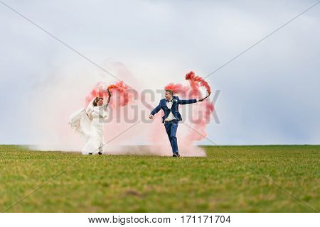 The bride and bridegroom running with red smoke bombs on the background of green field