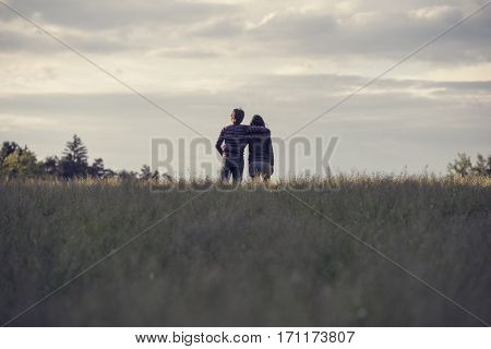 Rear view of young people boy and girl in casual standing hugging in the distance of countryside field against evening sky.