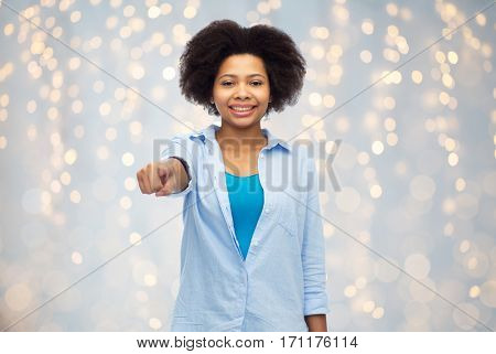 people, race, ethnicity, gesture and choice concept - happy african american young woman pointing finger to you over holidays lights background
