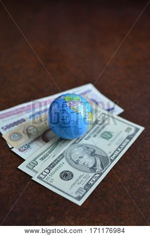 A miniature globe placed on an assorted gulf currency notes along with US dollars.
