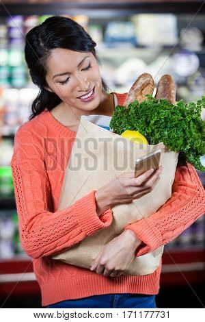 Woman using mobile phone while holding groceries in paper bag