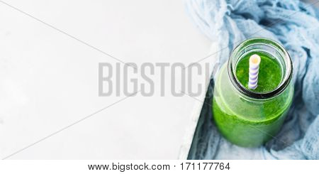 Healthy food concept green smoothie breakfast on white gray tray blue textile. Fruit vegetable juice glass bottle. Top view