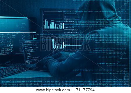 Internet concept. Hacker working on a code on dark digital background with digital interface around.