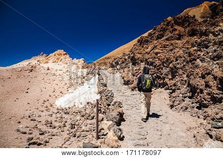 tourist man with backpack going to the top of the volcano Teide in Tenerife Canary Islands Spain
