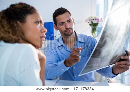 Physiotherapist explaining x-ray to patient in clinic