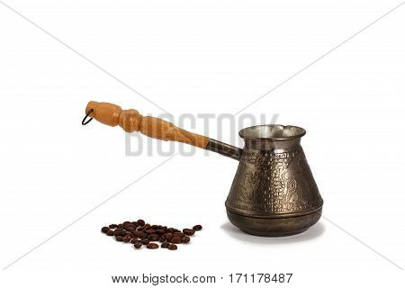 Cezve with coffee beans on white isolated background