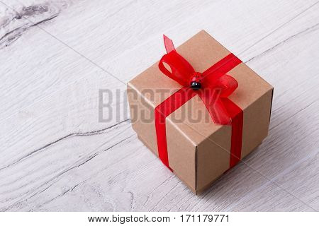 Gift box on wooden plank. Red ribbon on present box. Decorate your present with bow. Ladybug as accesorize.