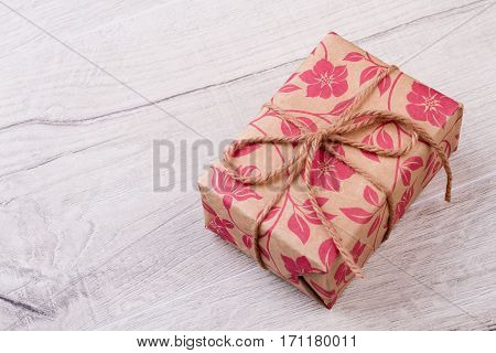 Gift wrapped with rope. Present box on wooden backdrop. Holiday is time of joy. Happiness from receiving a gift.