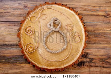 8-shaped rope on trunk slice. Rope patterns on wood. Use available materials for craft. Original handmade gift.