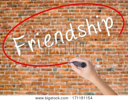 Woman Hand Writing Friendship With Black Marker On Visual Screen