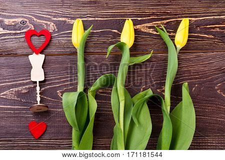 Heart on stand and flowers. Tulips near hearts on wood. Cherish your relationships. Romantic way of congratulation.