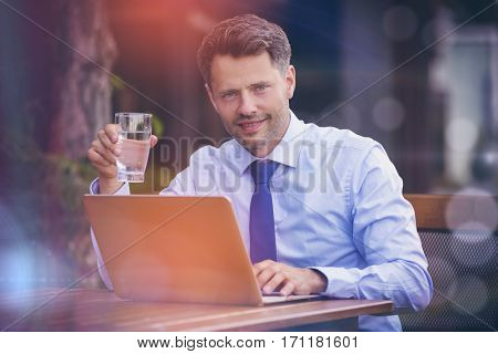 Portrait of businessman drinking water while using digital tablet at sidewalk cafe