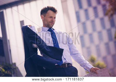 Low angle view of thoughtful businessman holding blazer and newspaper near office building