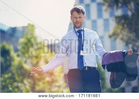 Portrait of confused businessman standing with blazer near office building