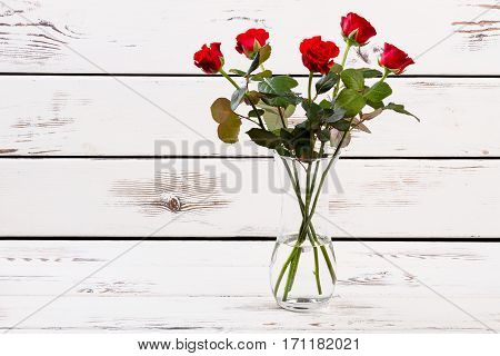 Glass vase with red roses. Roses on light wooden surface. Enjoying results of garden work. Floral present for sweetheart.