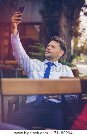 Businessman taking selfie at sidewalk cafe