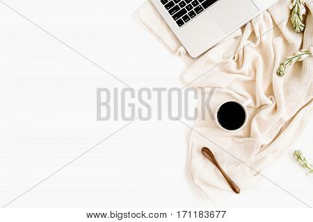 Workspace with laptop coffee spoon white flowers and beige textile on white background. Flat lay. Top view office table desk.
