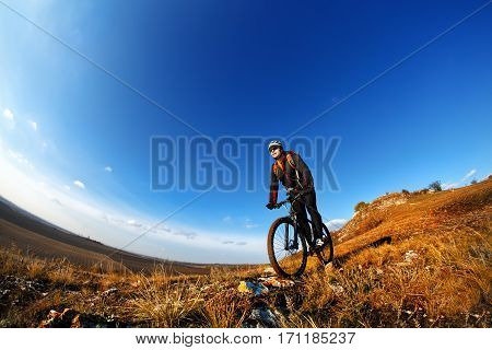 Mountain Bike and blue sky background. photographed on a fisheye lens. Cyclist in the helmet. Landscape with hill, mound and blue sky. Countryside.