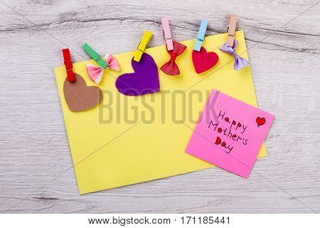 Happy Mother's Day colorful card. Note with greeting and clothespins. Think colorful and creative. Show that you care.