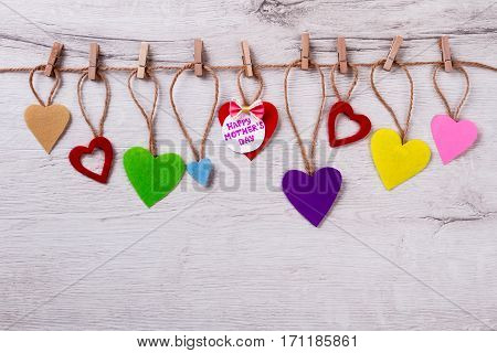 Mother's Day card on rope. Heart, bow tie, greeting paper. Be original when congratulating. Beautiful holiday for priceless person.