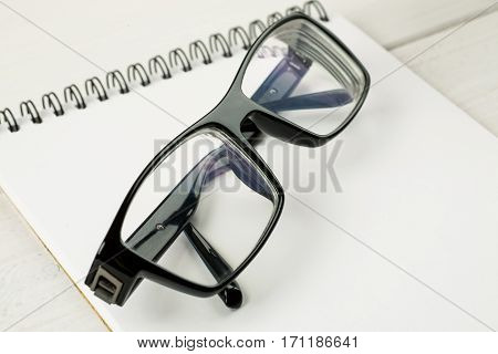 Black-rimmed Glasses Laying On A Notepad Blank Sheet On A Wooden Table